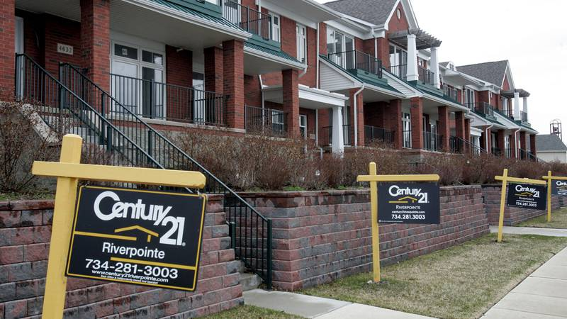 Real estate sale signs line in front of a condo