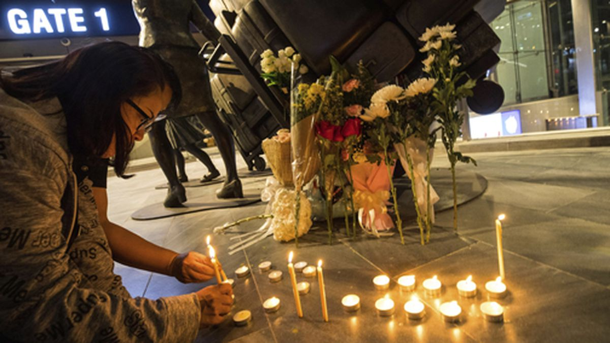 People attend a memorial service at Terminal 21 Korat mall in Nakhon Ratchasima, Thailand, Sunday, Feb. 9, 2020. Thai officials say a soldier who went on a shooting rampage and killed more than two dozen people and injured many others has been shot dead inside a mall in northeastern Thailand. (AP Photo/Wason Wanichakorn)
