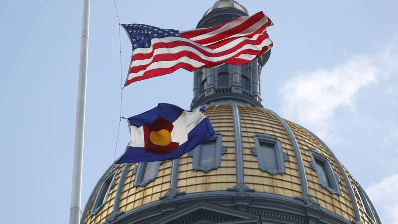 Stock Photo: Flags fly at half-staff in front of the dome of the Colorado State Capitol while...