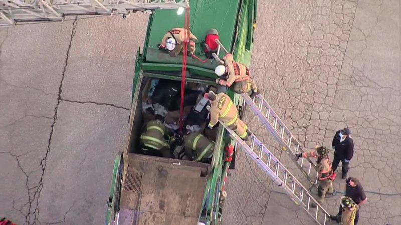 Firefighters rescued a man trapped in the back of a garbage truck Thursday in Oklahoma City....