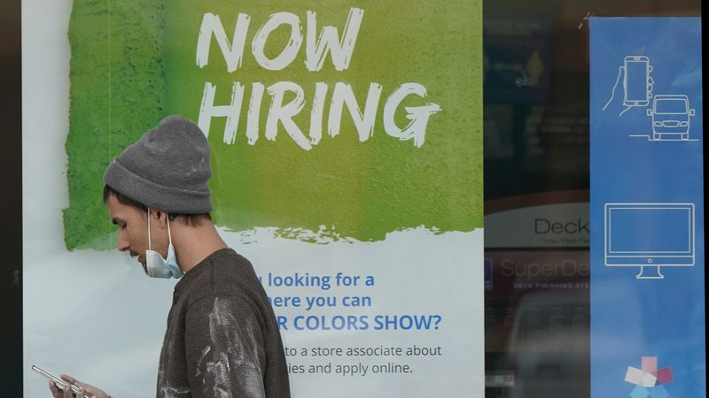 """FILE - A man walks past a """"Now Hiring"""" sign on a window at a Sherwin-Williams store, Friday,..."""