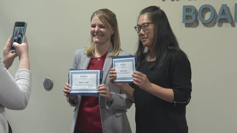 Melanie Trujillo and Ashley Zhang pose for a picture with their certificates.