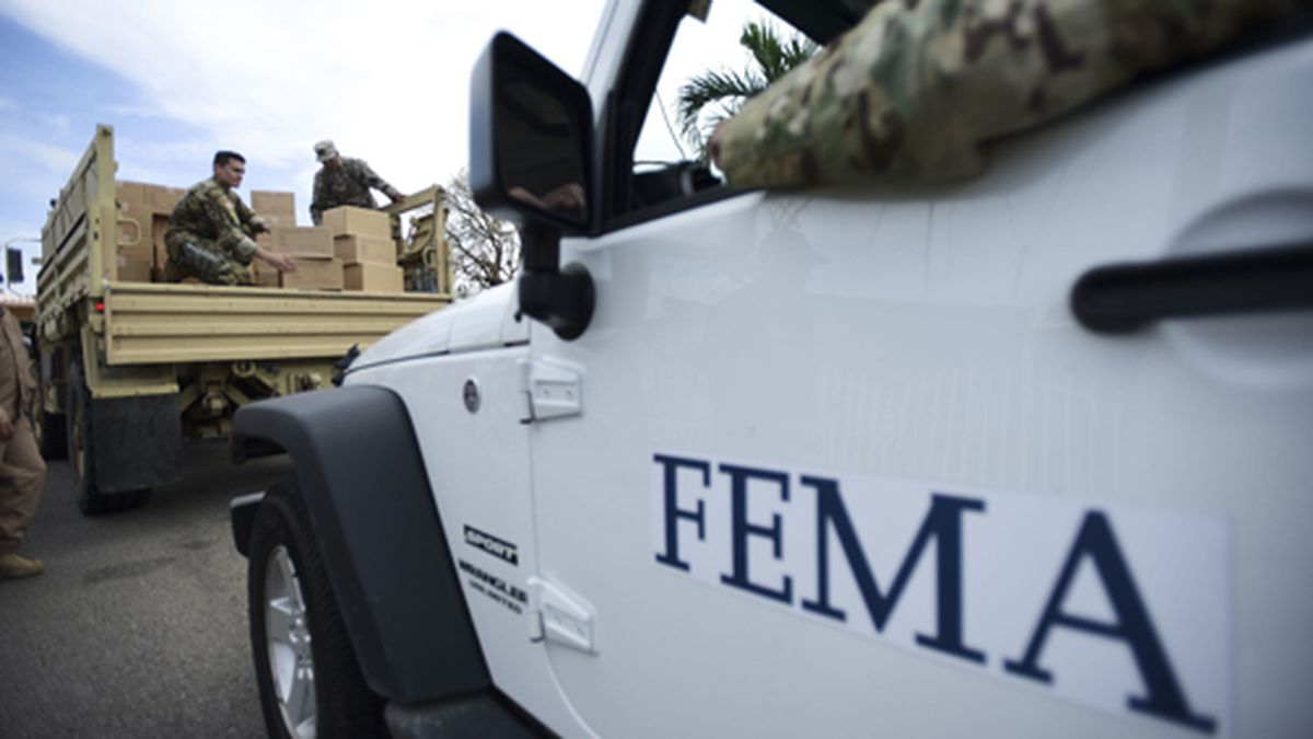 In this Oct. 5, 2017 file photo, Department of Homeland Security personnel deliver supplies to Santa Ana community residents in the aftermath of Hurricane Maria in Guayama, Puerto Rico. Federal authorities said Tuesday, Sept. 10, 2019, that they have arrested two former officials of the Federal Emergency Management Agency and the former president of a major disaster relief contractor, accusing them of bribery and fraud in the efforts to restore electricity to Puerto Rico in the wake of Hurricane Maria. (Source: AP Photo/Carlos Giusti, File)